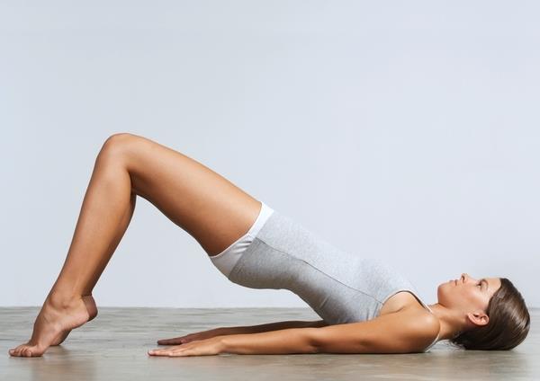 Femme en tenue de sport en train faire la planche et de travailler ses abdos.