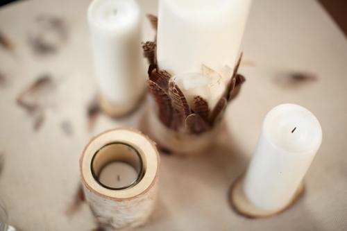Photo de bougeoirs customisés avec des petits rondins en bois et plumes