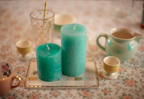 Bougies turquoises posées sur une plaque en verre