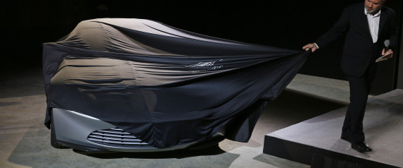 "Director Sam Mendes unveils an Aston Martin DB10 car during an event to mark the start of production for the new James Bond film ""Spectre"" at Pinewood Studios"