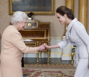 LONDON, ENGLAND - OCTOBER 10:  Actress Angelina Jolie is presented with the Insignia of an Honorary Dame Grand Cross of the Most Distinguished Order of St Michael and St George by Queen Elizabeth II in the 1844 Room on October 10, 2014 at Buckingham Palace, London. Jolie is receiving an honorary damehood (DCMG) for services to UK foreign policy and the campaign to end war zone sexual violence.  (Photo by Anthony Devlin - WPA Pool/Getty Images)
