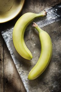 Two unopened bananas on a wooden board on a kitchen worktop