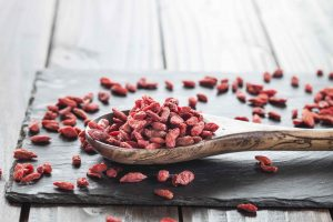 Wooden spoon with goji berries on a slate, superfood