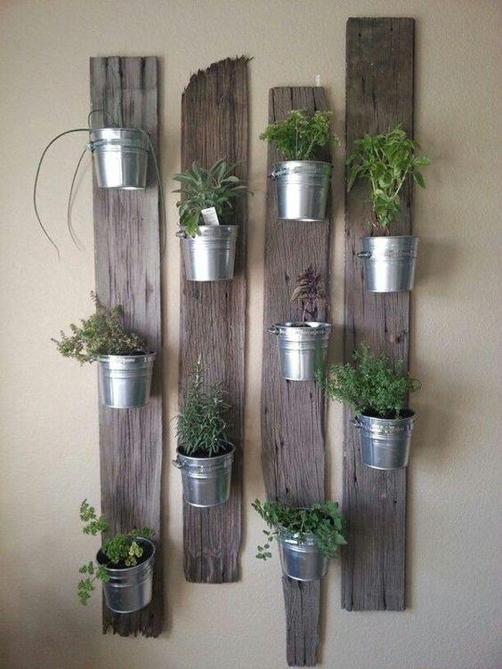 Dans des pots métalliques accrochés à des planches en bois.