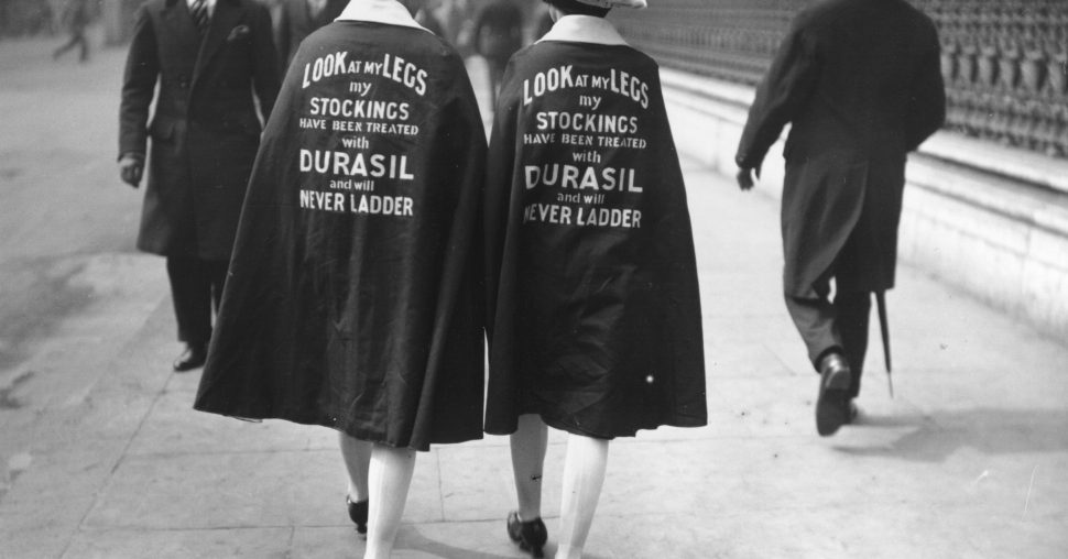 Two women wearing cloaks, advertising new never-ladder stockings with the words 'Look At My Legs - My Stockings Have Been Treated With Durasil And Will Never Ladder'.   (Photo by Topical Press Agency/Getty Images)