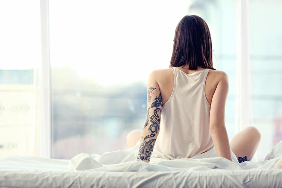 Femme tatouée assise de dos sur un lit.