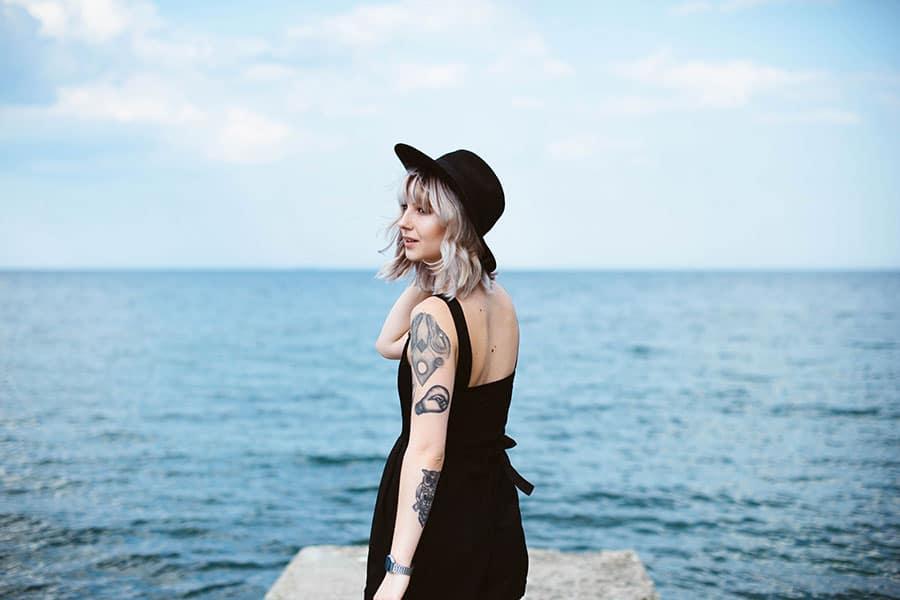 Jeune femme blonde tatouée au bord de mer.