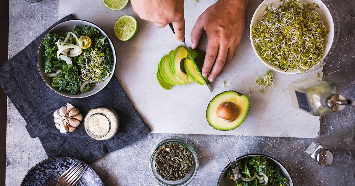 Préparation d'une salade végétarienne à base d'avocat et de graines germées.