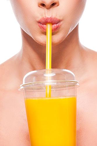 Une femme buvant un jus d'orange frais car miser sur les antioxydants est un bon plan pour réussir une détox.