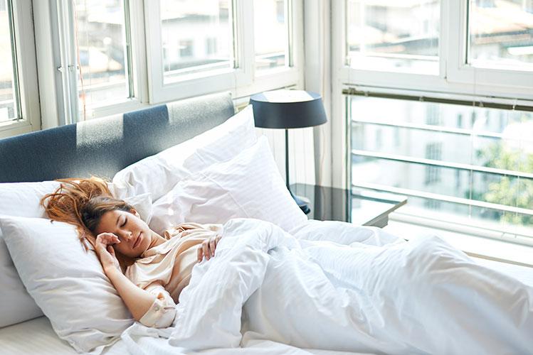 Jeune femme assoupie sur le dos dans un lit.