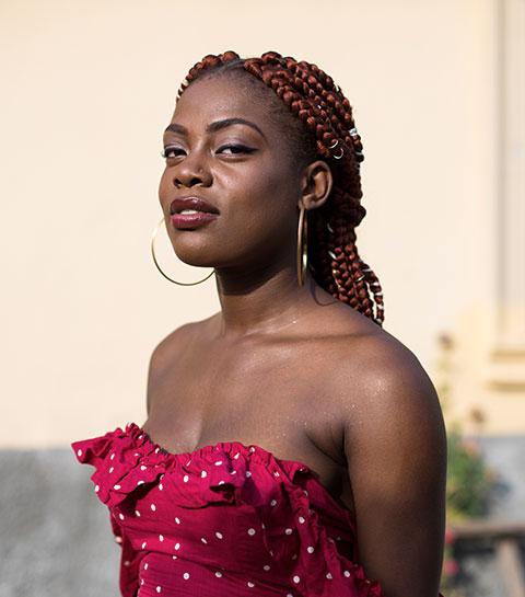 Photo d'une jeune femme d'origine africaine portant des tresses et une robe rouge.