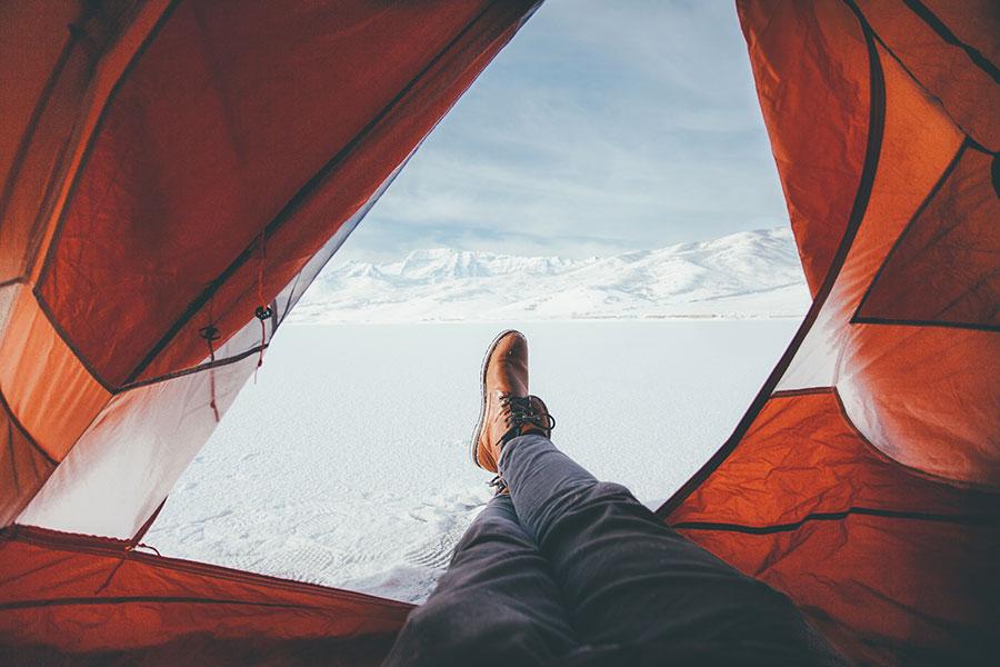 Vue d'une personne couchée et voyageant seule sur l'extérieur de sa tente.
