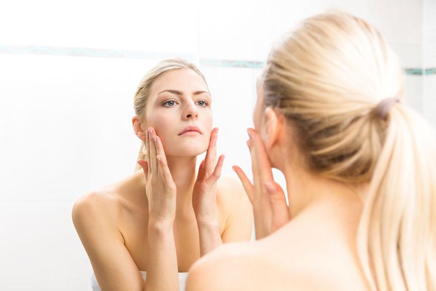 Jeune femme blonde inspectant sa peau dans un miroir.
