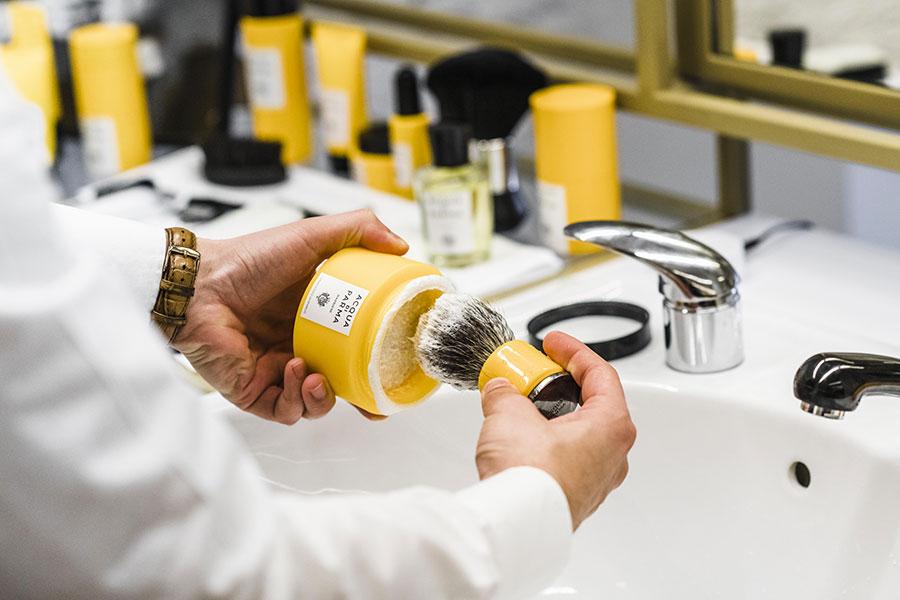 Mains d'home en train de faire mousser un blaireau avant de procéder au rasage.