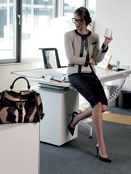 Jeune femme habillée en tailleur buvant un café au bureau.