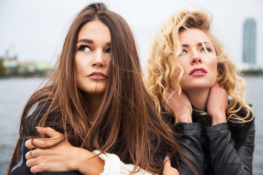 Deux jeunes filles regardant vers le ciel. L'une brune aux cheveux lisses, l'autre blonde aux cheveux ondulés.