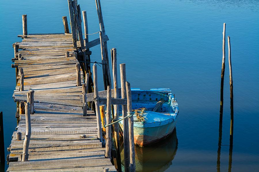 Photo d'un petit bateau amarré à un embarcadère à Comporta au Portugal.