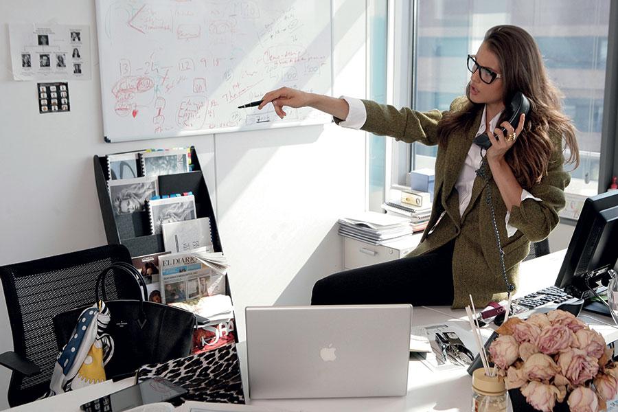Jeune femme assise sur un bureau passant un coup de fil professionnel.