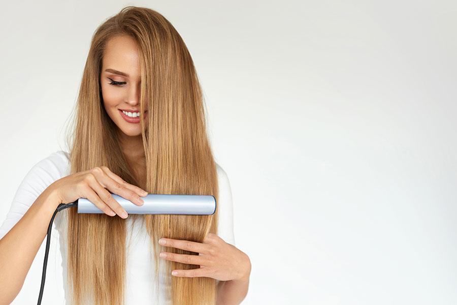 Jeune femme en train de lisser ses longs cheveux avec un liseur.