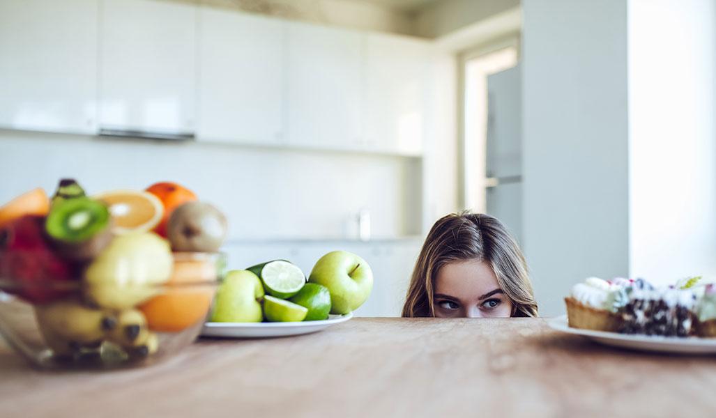 Jeune femme face à un plat de fruit et une assiette de pâtisseries.
