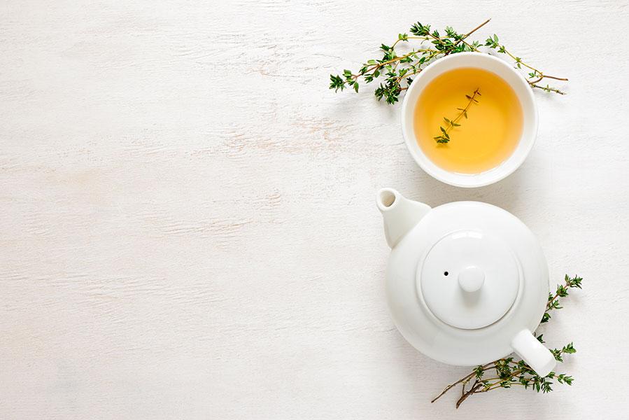 Théière et tasse de thé aux herbes.