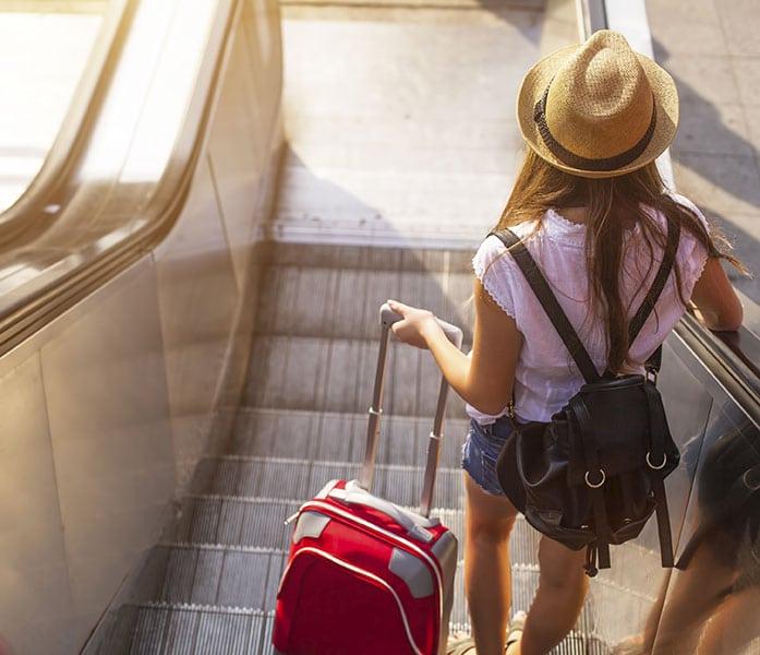 Jeune fille portant un short et un chapeau et tirant une valise.