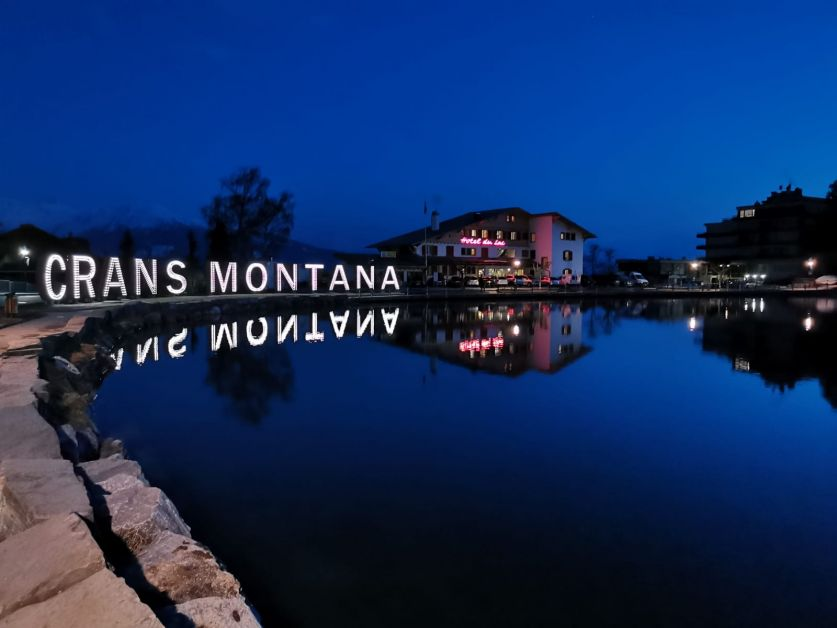 Photo d'un hôtel de Crans-Montana illuminé la nuit.