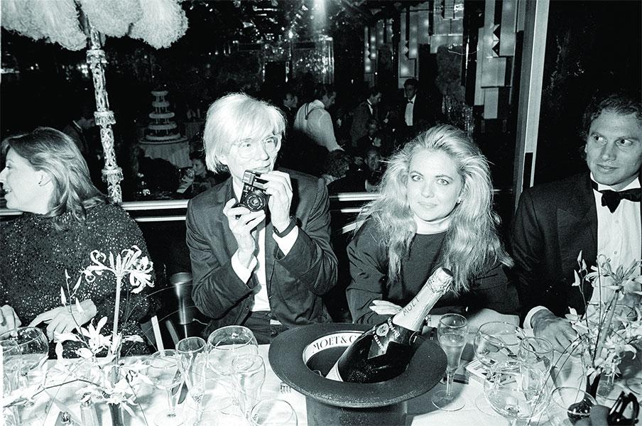Andy Warhol buvant du champagne Moët & Chandon lors d'un diner de gala.