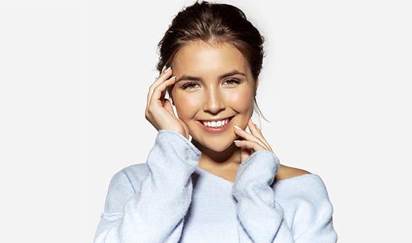 Jeune femme souriante ayant une très belle peau sans imperfection.