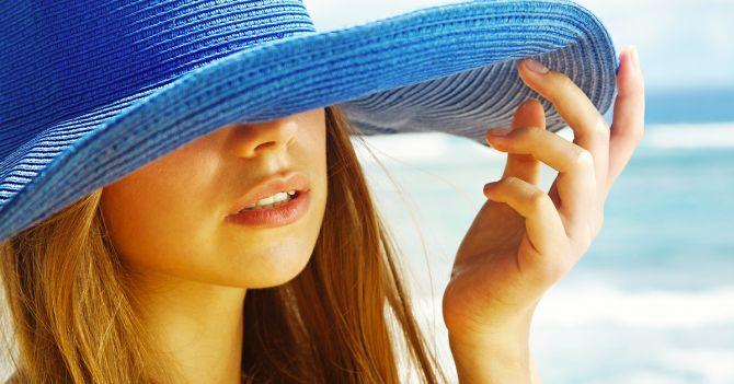 Jeune femme portant un chapeau exposée au soleil.