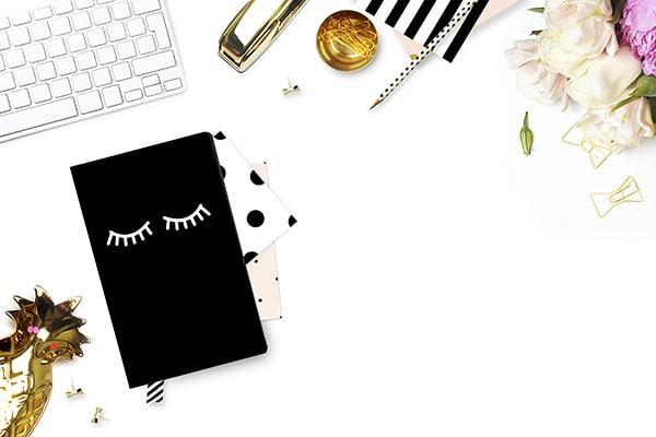 Quelques accessoires type bloc-notes, crayons et objets de décoration disposés sur un bureau.