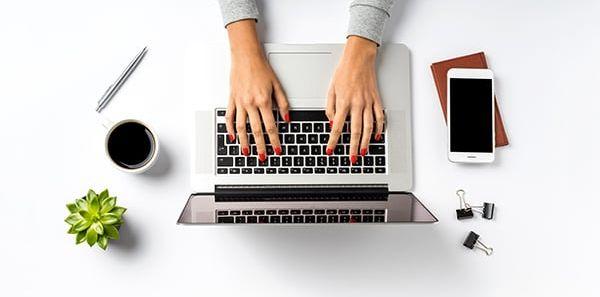 Photo d'une jeune femme attablée à son bureau en train de taper à l'ordinateur.