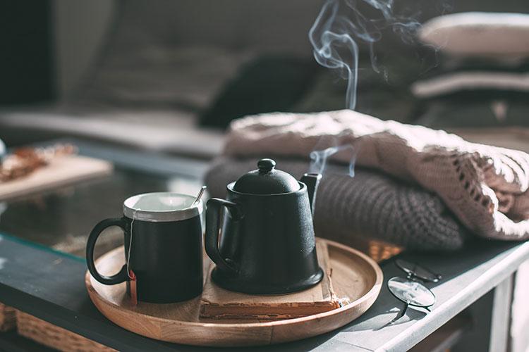 Plateau en bois contenant une théière et une tasse de thé fumant