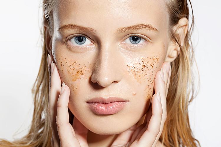 Jeune femme réalisant un peeling doux gommant du visage.