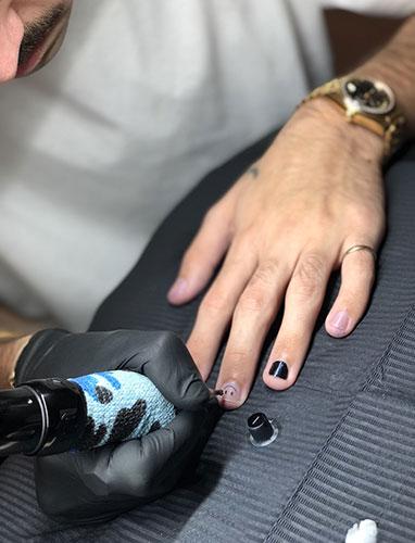 Minus en train de réaliser un tatouage sur ongle sur lui-même.