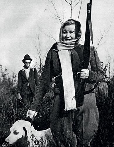 Rachele Mussolini, femme du dictateur Mussolini, tenant un chien et une arme en mains.
