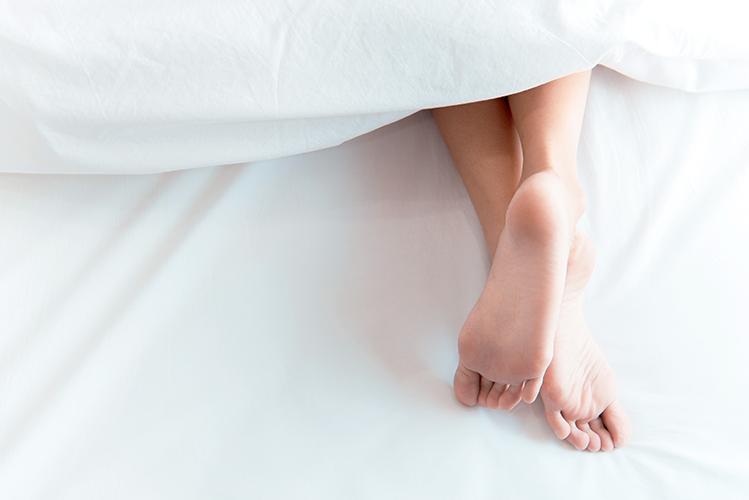 Pieds de femme dépassant de la couette dans un lit.