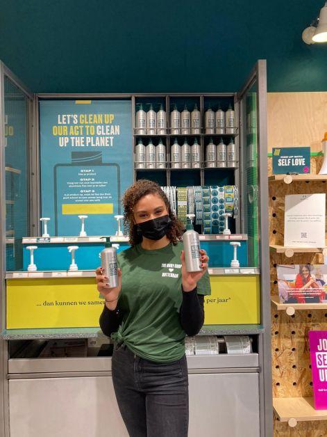 stand de recharge The Body Shop avec une employée qui tient en main deux flacons de recharge