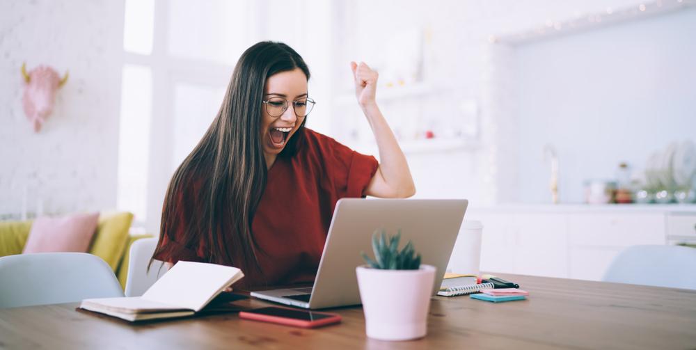 femme devant son ordinateur qui est heureuse