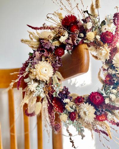 Couronne de fleurs séchées posée sur une chaise en bois.
