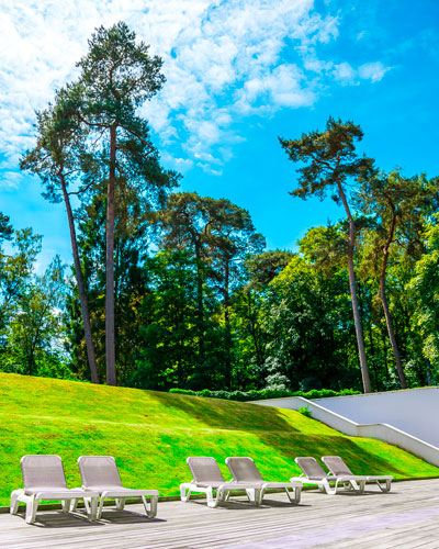 La terrasse en plein air du Dolce La Hulpe Brussels attenante à la piscine couverte et avec vue sur le forêt de Soignes.