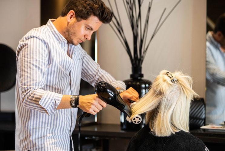 Romain Vanrysselberghe en plein coiffage dans son salon bruxellois.