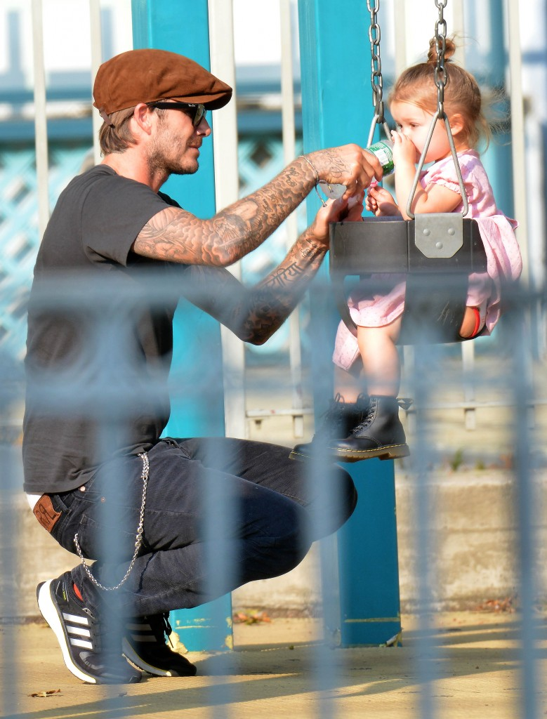 CUTE PICTURES OF SUPER DAD DAVID BECKHAM PLAYING WITH BABY HARPER ON THE SWINGS PLS NOTICE: HARPER'S TATTOO BY DAVID'S NECK VICTORIA'S TATTOO BY DAVID'S HAND LITTLE HARPER DR. MARTENS BOOTS