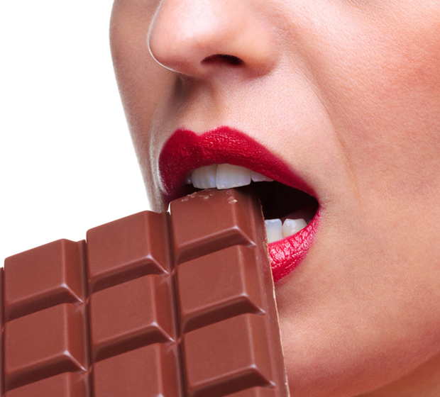 Close up of a woman with red lipstick eating a bar of chocolate white background
