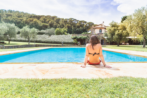 Young woman relaxing in a resort swimming pool
