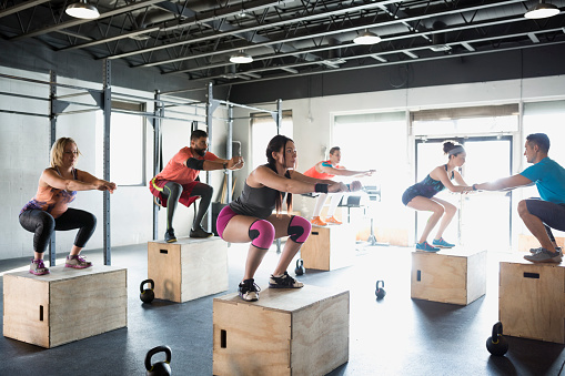 Crossfit exercise class doing jump squats on boxes