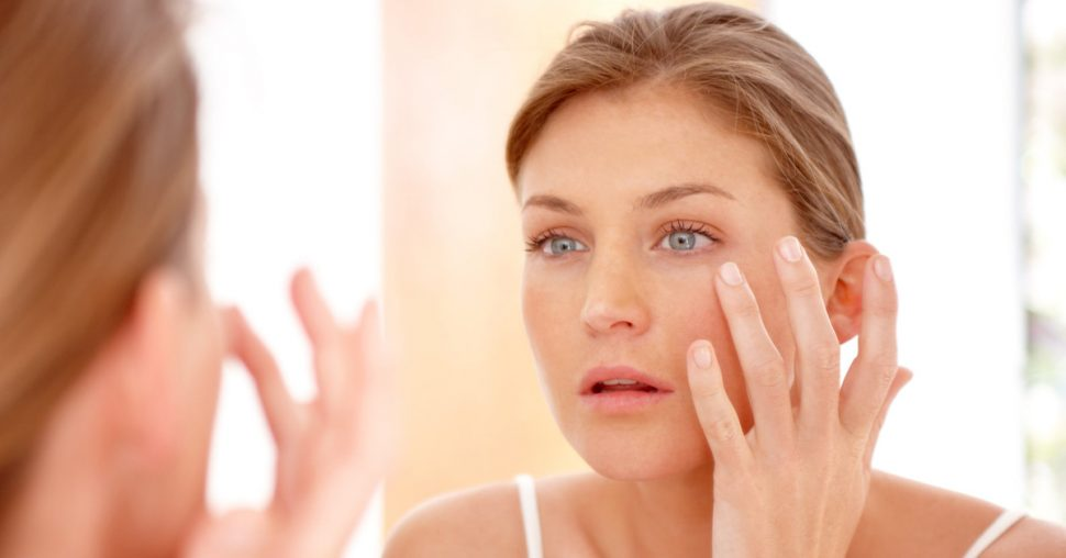 A naturally gorgeous woman applying moisturizing cream in a mirror