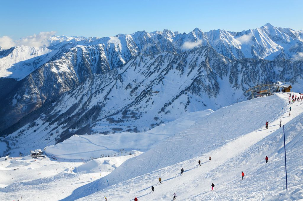 Skiers are sliding down snow-covered hill on skis at the Cirque du Lys. There is range of mountains (Soum de Mauloc) in the background. Winter Pyrenees is photographed at the Cauterets ski resort.
