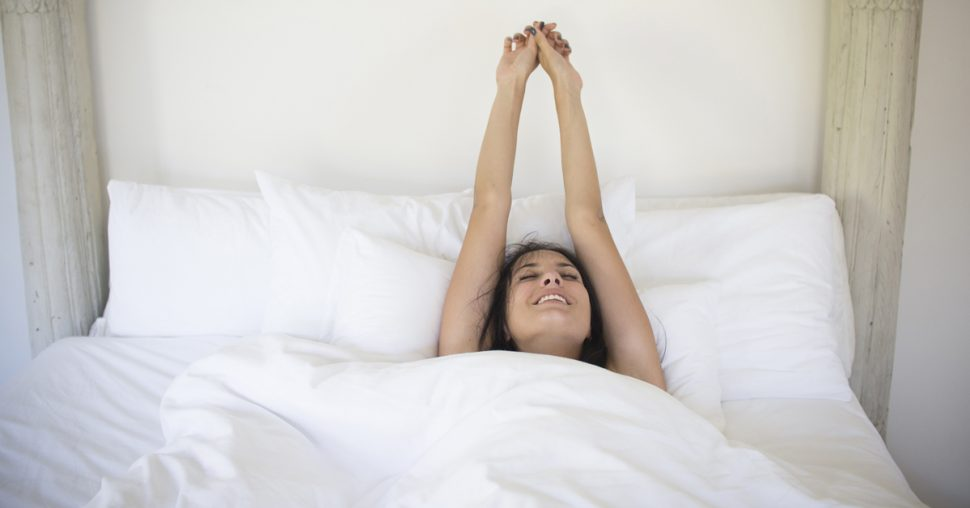 Woman stretching and waking up in bed at home