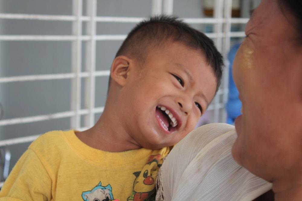 patientje lacht op de schoot met zijn mama